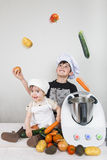 Two children cooking with a futuristic machine Royalty Free Stock Images