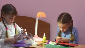 Two children cut with scissors pieces of colored paper. Making crafts stock video