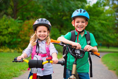 Two children cycling in park. Two cute children cycling in summer park Stock Photos