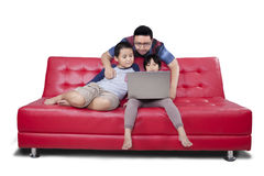 Two children and dad browsing internet online Stock Photo