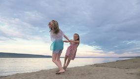 Two children dance and indulge on the beach. Children perform dancing stunts tricks. Hair fluttering in the wind. The kid spin and jump, shake their heads. One stock footage
