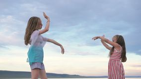 Two children dance and indulge on the beach. Children perform dancing stunts tricks. Hair fluttering in the wind. The kid spin and jump, shake their heads. One stock video footage