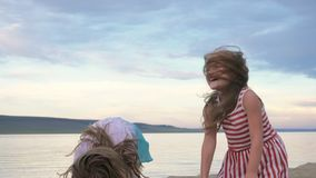 Two children dance and indulge on the beach. Children perform dancing stunts tricks. Hair fluttering in the wind. The kid spin and jump, shake their heads. One stock video