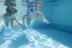 Two children diving in masks underwater Stock Photography