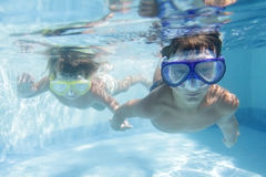 Two children diving in masks underwater Stock Photos