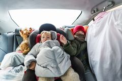 Two children in warm clothes is in the car in wintertime royalty free stock image