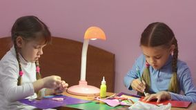 Two children doing crafts, one cuts with scissors colored cardboard, the second marks cut point pencil stock video footage