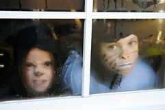 Children behind a window with raindrops
