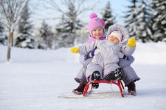 Two children dressed in warm clothes near forest sit on red sled Stock Images