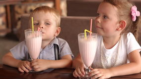Two children drinking milkshakes in cafe outdoors. stock footage