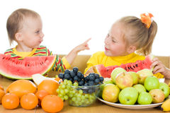 Two children eat fruit at a table Royalty Free Stock Images