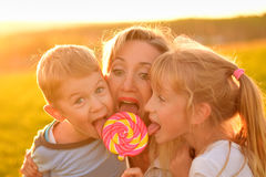 Two children eat lollipop with mother Stock Photos