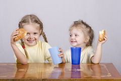 Two children eat a muffin at the table Royalty Free Stock Images