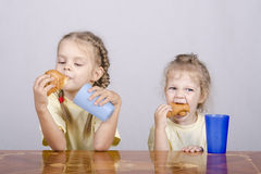 Two children eat a muffin at the table Royalty Free Stock Photography