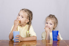 Two children eat a muffin at the table Stock Photo