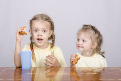 Two children eat a muffin at the table Royalty Free Stock Photos