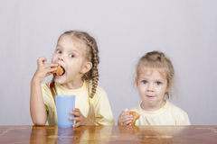 Two children eat a muffin at the table Stock Image