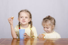 Two children eat a muffin at the table Stock Images