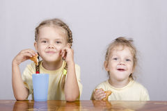 Two children eat a muffin at the table Stock Photography