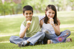 Two children eating ice cream in park royalty free stock photo