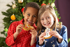 Two Children Eating Treats In Front Of Tree royalty free stock image