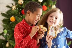 Two Children Eating Treats In Front Of Tree Stock Photography