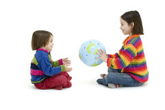 Two children embracing the world globe. Isolated on white Royalty Free Stock Photo