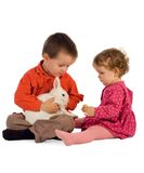 Two children feeding a bunny. Two children - boy and girl - feeding a cute bunny (easter theme, isolated stock image
