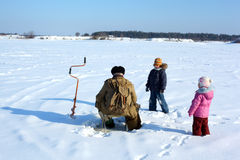 Two children and fisherman on frozen river Stock Photos