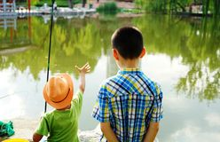 Two children are fishing on the bank Stock Image
