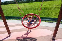 Two children fun on swing round Royalty Free Stock Photo