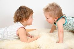 Two children on fur carpet Royalty Free Stock Images