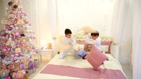 Two children of gay child of twin brother are having fun and fighting with pillows on bed in bright room with Christmas. Joyful and happy children play and fool stock footage