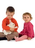 Two children getting acquainted with a bunny. Two children, boy and girl get acquainted with a bunny (easter theme, isolated stock image