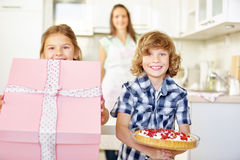 Two children with gift and cake Royalty Free Stock Photos