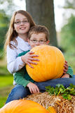 Two children happy with their pumpkin. Two children sitting on straw and holding a pumpkin Royalty Free Stock Photography