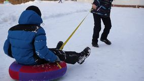 Two children have fun playing on snowtube spinning in a circle. Slowmotion. Two children have fun playing on snowtube spinning in a circle stock video footage