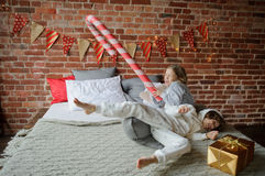 Two children have put up cheerful fight on a big bed. Christmas morning. Two children have put up cheerful fight on a big bed. Brick wall is decorated with royalty free stock photography
