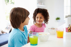 Two Children Having Breakfast In Kitchen Together Stock Image
