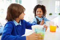 Two Children Having Breakfast Before School In Kitchen. Looking At Each Other Whilst Sitting At Table With Cereal And Glass Of Orange Juice Stock Photo