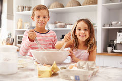 Two children having fun baking in the kitchen Stock Image