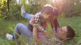 Two children are having fun with dad on the grass. Two children are playing and having fun with dad on the grass in the Park stock footage