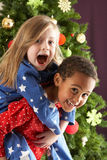 Two Children Having Fun In Front Of Christmas Tree Stock Photography