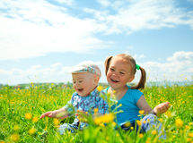 Two children are having fun on green meadow Royalty Free Stock Images