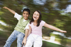 Two children having fun on roundabout. Two children having fun on spinning roundabout in playground Royalty Free Stock Photography
