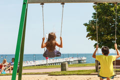 Two children having fun on swingset. Royalty Free Stock Image