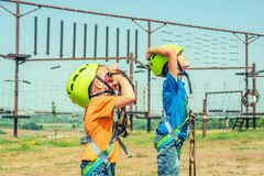 Two children in helmets and safety gear are looking up in an extreme park royalty free stock photos