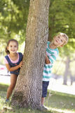 Two Children Hiding Behind Tree In Park Stock Photography