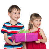 Two children hold a gift box. On the white background stock images
