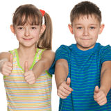 Two children hold their thumbs up Stock Photos